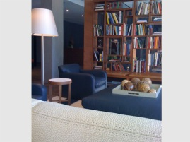 Custom Bookcase acts as a divider in the glass lobby