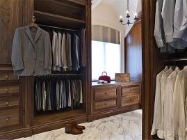Walnut cabinetry in master walk-in closet