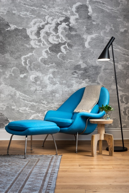 Modern floor lamp, table and bespoke bright blue lounge chair against Fornasetti wallpaper mural.