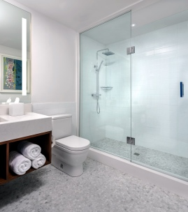 Mosaic tile flooring throughout with Caesarstone sill, large tile glass shower enclosure and backlit bathroom mirror.