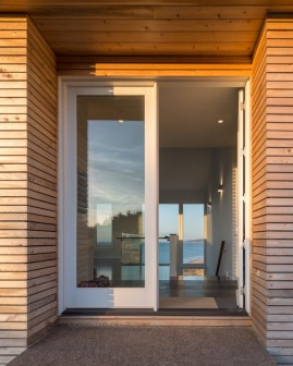 Sheltered entrance in glass and red cedar blocks the wind and preserves the view.