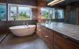 Contemporary free-standing tub, basalt hexagonal tile, natural stone counter with under-mount sink and floating walnut vanity, walnut accent wall and bathroom mirror with built-in nightlight.